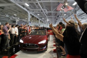 Tesla workers cheer for one of the first Tesla Model S cars sold, seen here at the Tesla factory in Fremont, Calif., June 22. Op-ed contributors John Rogers and David Friedman say 'clean tech is on the rise nationwide in large part due to federal investment.' Yes, 'there are risks when government and industry invest boldly in new technology. But if they don't, America will cede its leadership on [clean tech] to other nations like China...' Paul Sakuma/AP/File