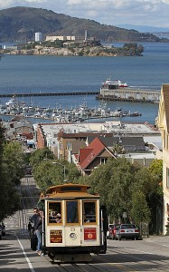 San Francisco cable car number 3 heading south on Hyde St, passing Russian Hill Park, with Hyde St Pier, Pier 45 on Fishermans Wharf, and Alcatraz Island in the background. San Francisco, California, USA.